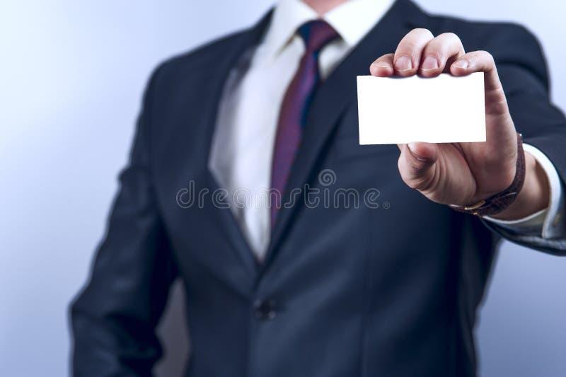 Mężczyzna w ciemnym kostiumu trzyma wizytówkę obrazy royalty free