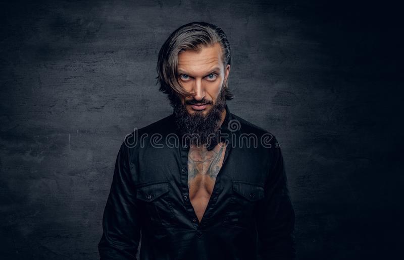 Mężczyzna w czarnej koszula z tatuażem na jego klatce piersiowej obraz royalty free