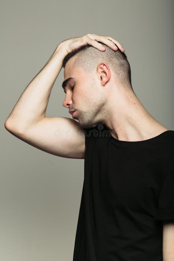 Mężczyzna w czarnej koszulce z ręką na jego głowie fotografia royalty free