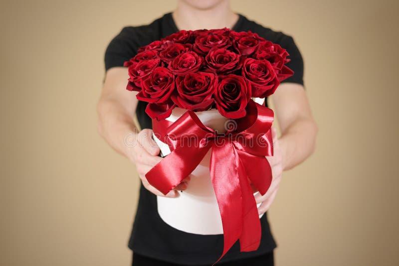 Mężczyzna w czarnym t koszulowym mieniu w ręka prezenta bogatym bukiecie 21 czerwień obrazy stock