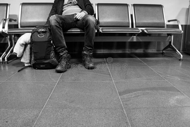 Mężczyzna w czekanie pozy obsiadaniu na krześle z plecakiem w lotnisku Czekania i odjazdu pojęcie fotografia stock