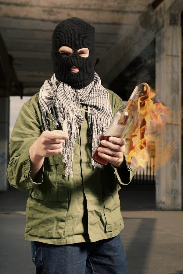 Mężczyzna w czerni masce działa flammable butelkę w rękach fotografia royalty free