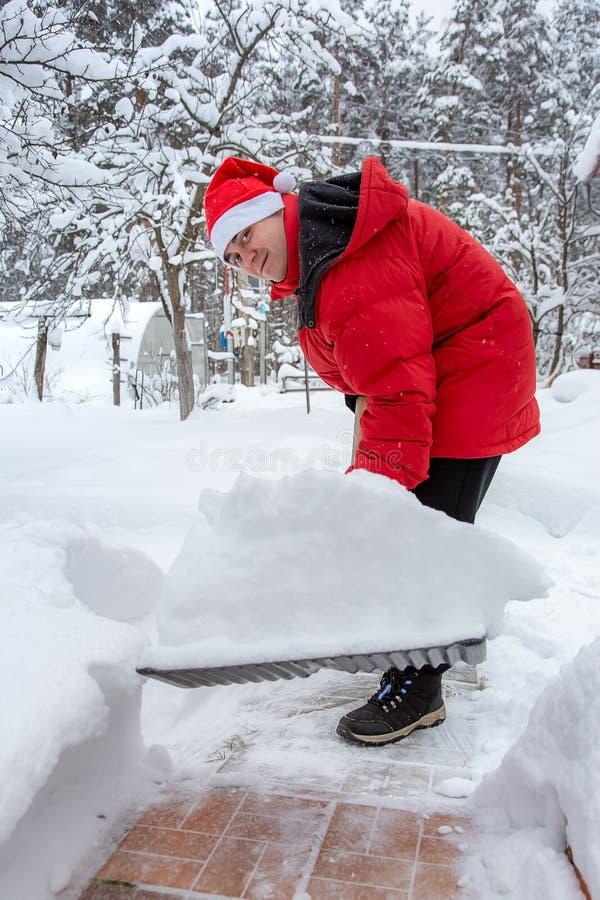 Mężczyzna w czerwień puszka kurtce i czerwień kapeluszu Santa Claus rozjaśnia śnieg w podwórko Rozjaśnia snowdrifts na ścieżce st zdjęcia royalty free