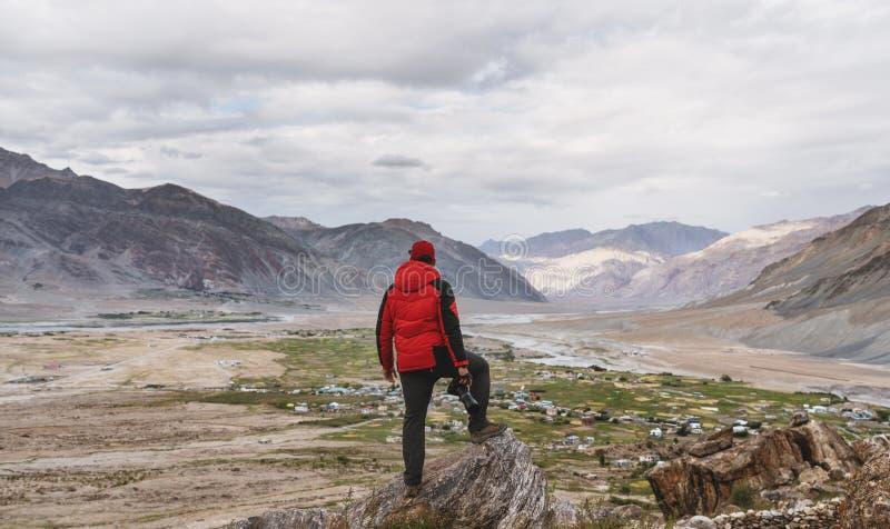 Mężczyzna w czerwonej kurtki pozycji na halnym szczycie i góra widok, Podróżuje styl życia, sukces i osiągnięcie, awanturniczy, zdjęcia stock
