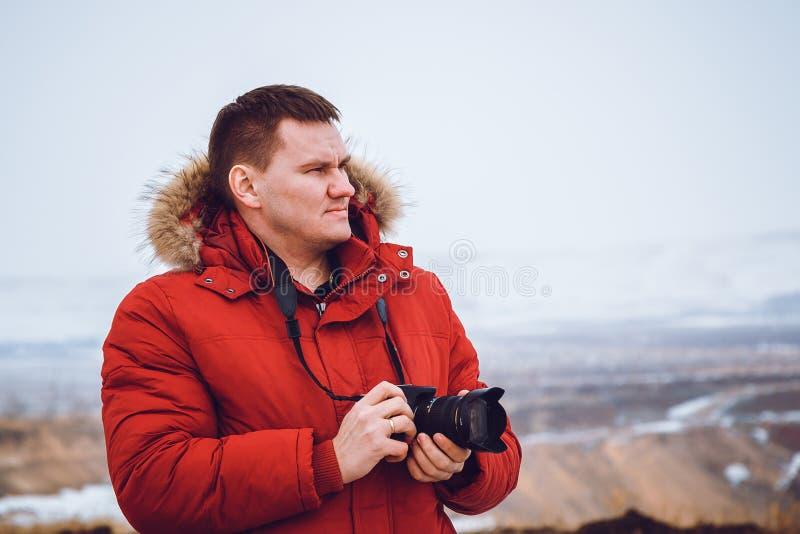 Mężczyzna w czerwonej puszek kurtce z kamerą podróżuje góry w zimie zdjęcie royalty free