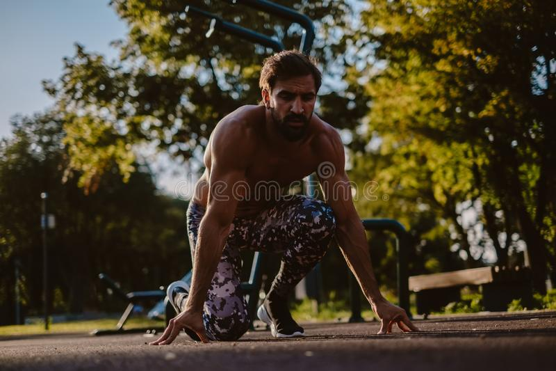 Mężczyzna w cztery punktów początku pozyci przy plenerowym gym fotografia stock