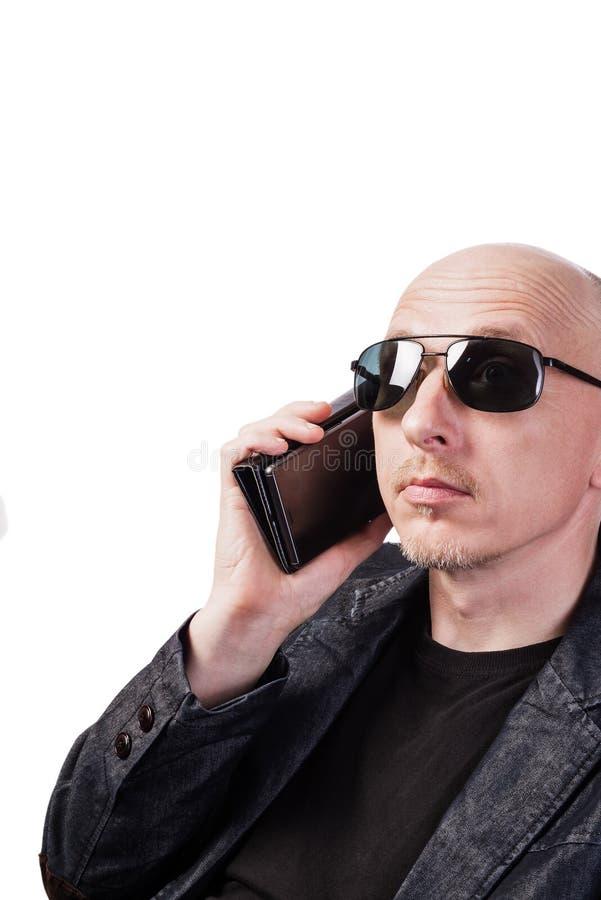 Mężczyzna w drelichowej kurtce, będący ubranym okulary przeciwsłoneczni, opowiada na telefonie komórkowym obraz stock