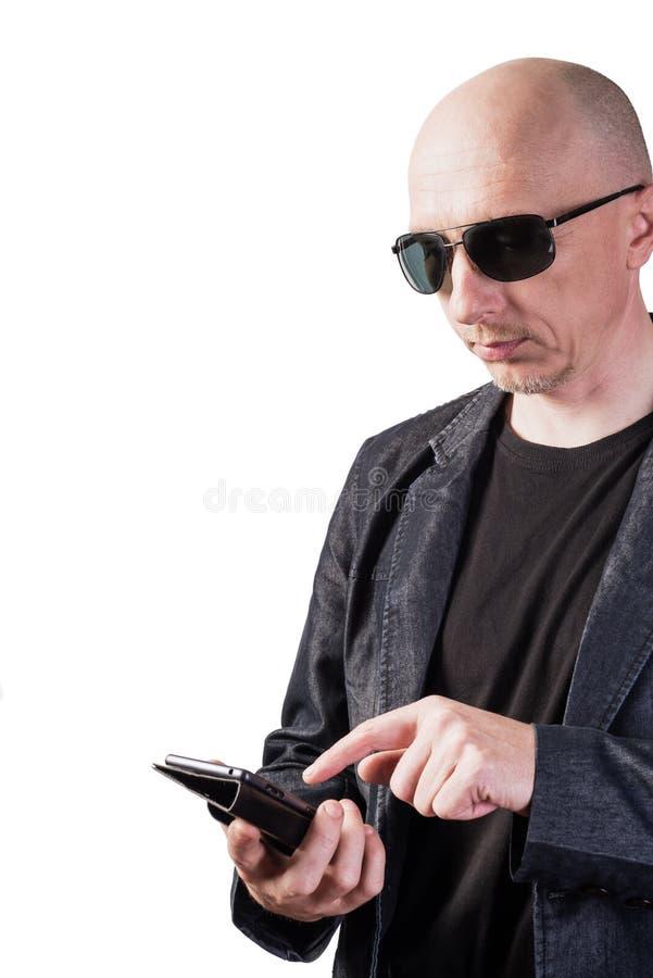 Mężczyzna w drelichowej kurtce, jest ubranym okulary przeciwsłonecznych, wybiera numer liczbę na smartphone obraz stock