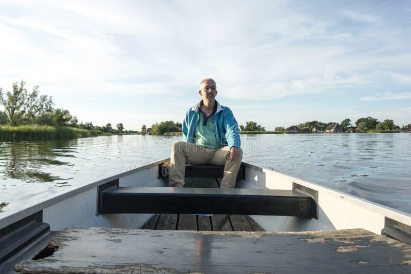 Mężczyzna w drewnianej łodzi na jeziorze obrazy royalty free