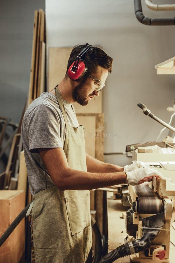 Mężczyzna w earmuffs pracuje na pasowym sander obrazy royalty free