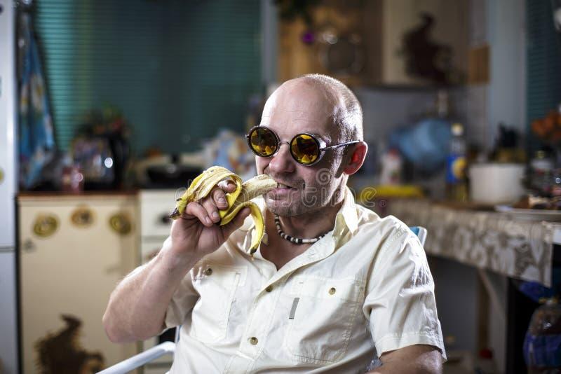Mężczyzna w eleganckich żółtych szkłach siedzi zrelaksowanego w karle i je banana z smirk na jego twarzy na rozmytym tle, fotografia royalty free
