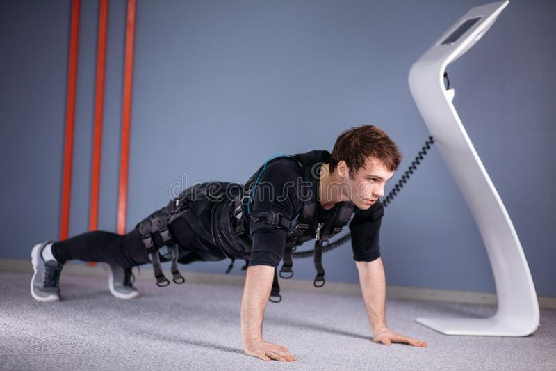 Mężczyzna w Elektrycznych Mięśniowych pobudzenie kostiumach robi desce ćwiczy ems zdjęcie stock