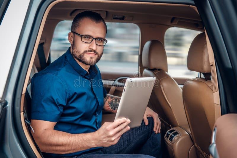 Mężczyzna w eyeglasses z tatuażem na jego ręce używać przenośnego pastylka peceta na tylnym siedzeniu samochód zdjęcia royalty free