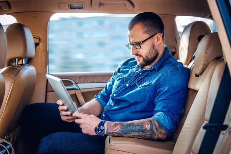 Mężczyzna w eyeglasses z tatuażem na jego ręce używać przenośnego pastylka peceta na tylnym siedzeniu samochód obraz stock