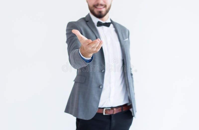 Mężczyzna w formalnej kostium pozycji i przedstawienia gestykulujemy szeroko rozpościerać ręki otwartej palmy na białym tle z kop zdjęcia royalty free