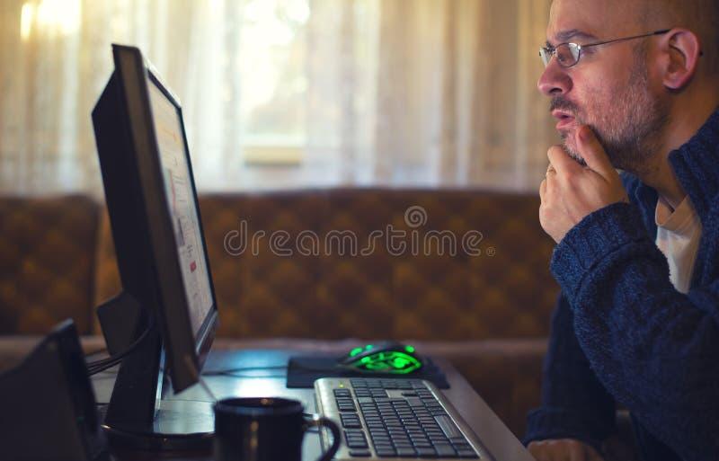 Mężczyzna w forties pracuje na komputerze w domu obraz royalty free