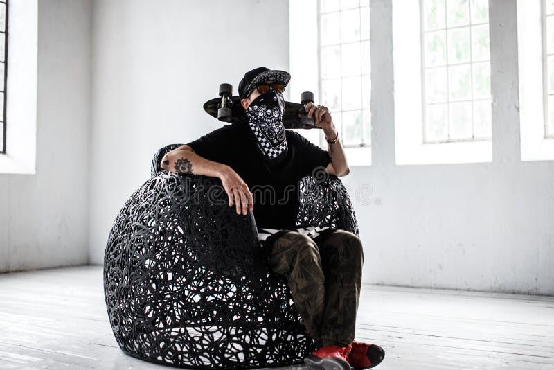 Mężczyzna w gangster masce z deskorolka fotografia stock
