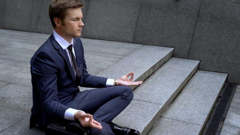 Mężczyzna w garnituru obsiadaniu w lotosowej pozycji w biznesie, zyskuje samokontrolę zdjęcia stock
