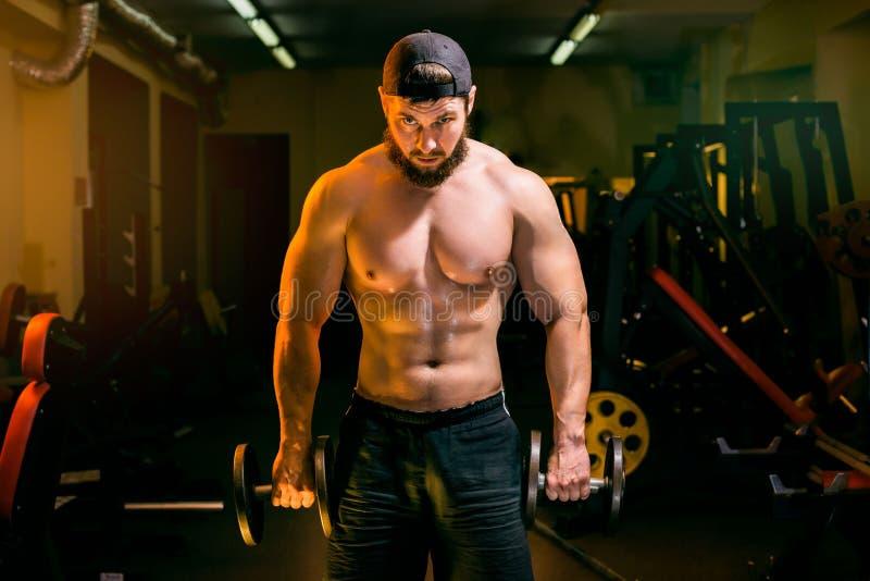 Mężczyzna w gym szkoleniu z dumbbells zdjęcia stock