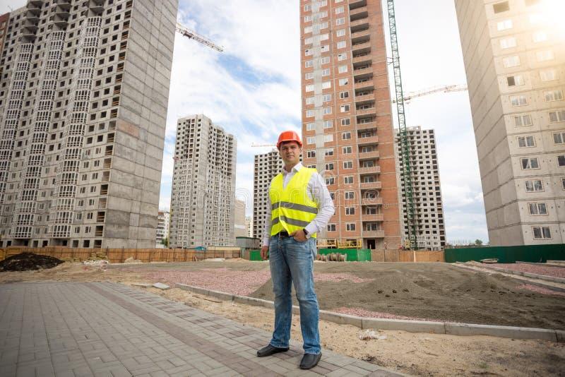 Mężczyzna w hardhat i zbawcza kamizelki pozycja na placu budowy zdjęcia stock