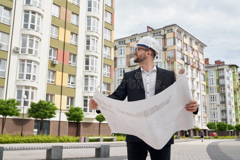Mężczyzna w hardhat z architektonicznymi budowa rysunkami obrazy royalty free