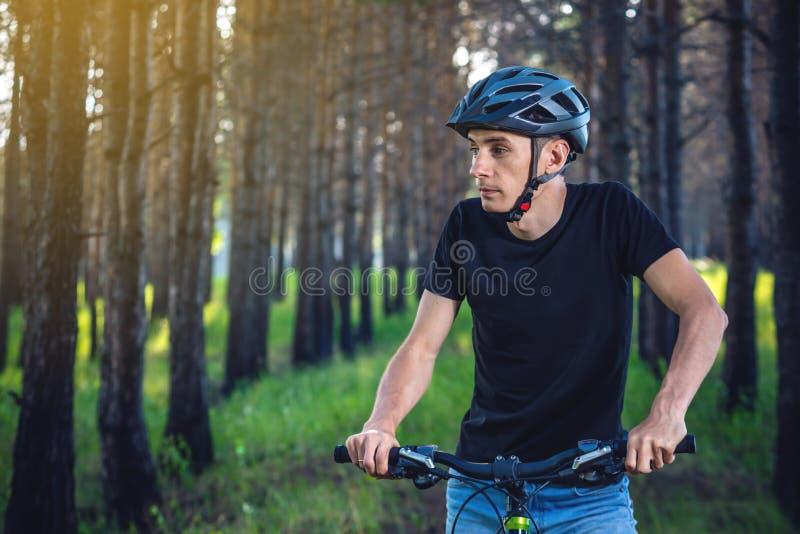 Mężczyzna w hełm jazdie na rowerze górskim w drewnach Cyklista w ruchu Pojęcie aktywny i zdrowy styl życia obrazy stock