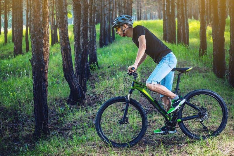 Mężczyzna w hełm jazdie na zielonym rowerze górskim w drewnach Cyklista w ruchu Pojęcie aktywny i zdrowy styl życia obrazy stock