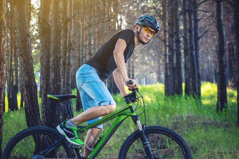 Mężczyzna w hełm jazdie na zielonym rowerze górskim w drewnach Cyklista w ruchu Pojęcie aktywny i zdrowy styl życia zdjęcia stock