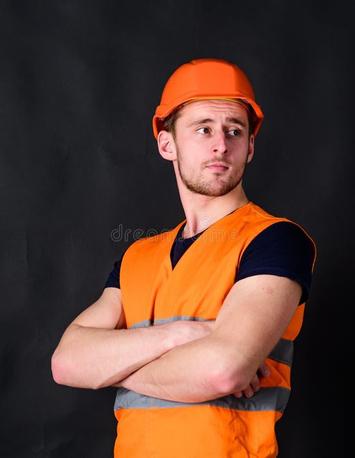 Mężczyzna w hełmie, ciężkiego kapeluszu chwyta ręki krzyżował na klatce piersiowej, czarny tło Pracownik, kontrahent, budowniczy  obrazy royalty free