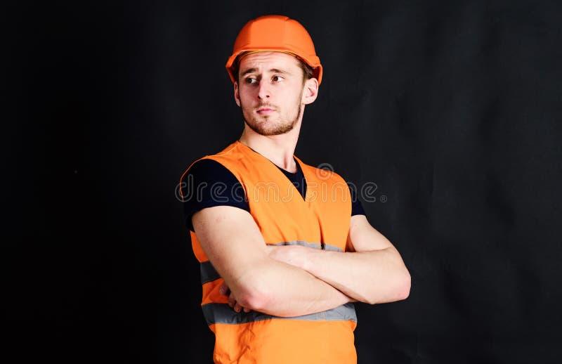 Mężczyzna w hełmie, ciężkiego kapeluszu chwyta ręki krzyżował na klatce piersiowej, czarny tło Pracownik, kontrahent, budowniczy  zdjęcia stock