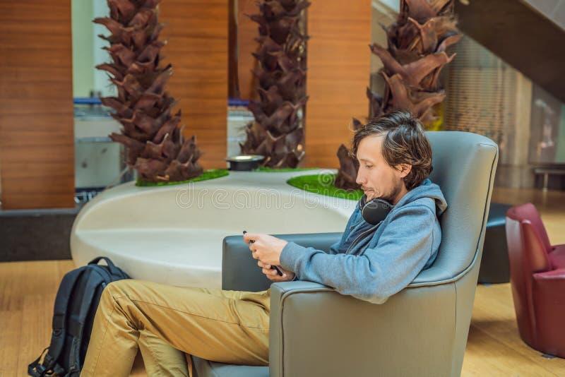 Mężczyzna w holu terenie przy lotniskiem czekać na jego samolot, używa, smartphone i hełmofony człowiek uśmiechnięci young zdjęcie stock