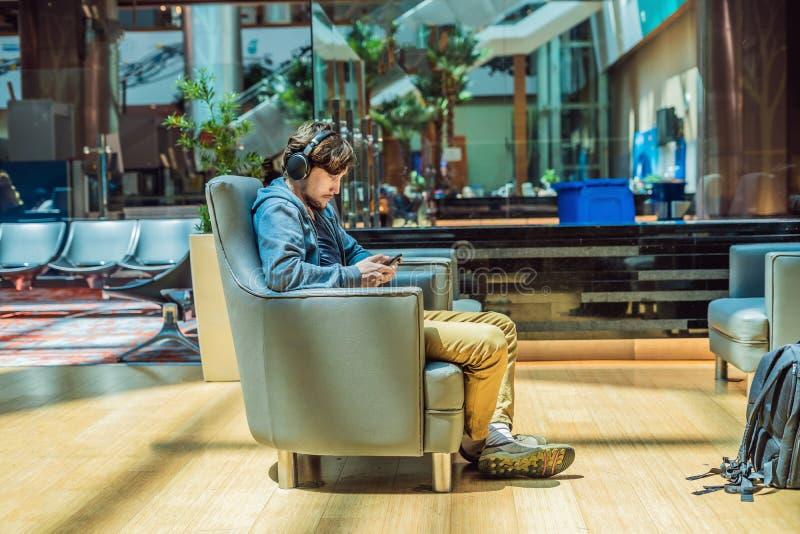 Mężczyzna w holu terenie przy lotniskiem czekać na jego samolot, używa, smartphone i hełmofony człowiek uśmiechnięci young fotografia royalty free