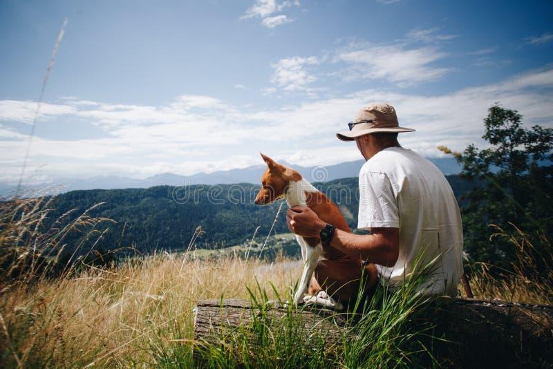Mężczyzna w kapeluszu siedzi z najlepszego przyjaciela psa szczeniakiem przy wierzchołkiem obraz royalty free