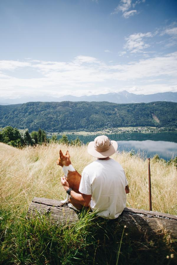 Mężczyzna w kapeluszu siedzi z najlepszego przyjaciela psa szczeniakiem przy wierzchołkiem zdjęcie royalty free