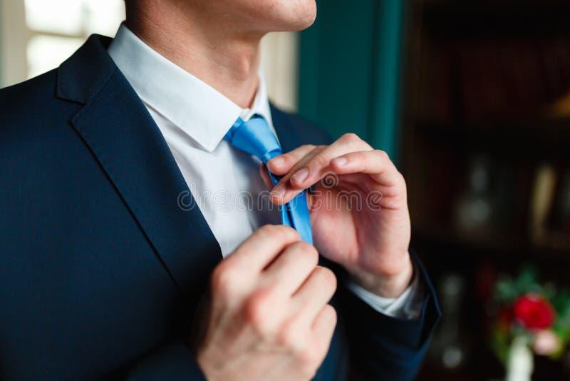 Mężczyzna w klasycznym kostiumu prostuje jego błękitnego krawat Przystojny elegancki potomstwo mody mężczyzna w żakieta smokingu  obrazy stock