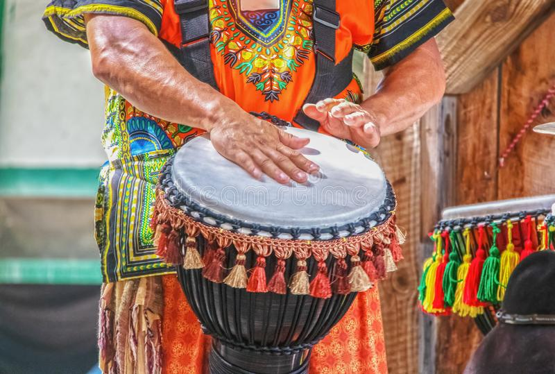 Mężczyzna w kolorowych kostium sztuk perkusji Afrykańskim etnicznym bębenie z kitkami przeciw zamazanemu tłu i ruch plamie - crop zdjęcia stock