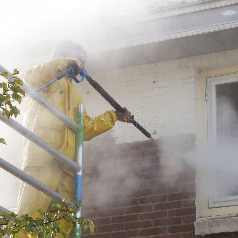 Mężczyzna w koloru żółtego deszczu kostiumu czyści farbę od ściana z cegieł dom fa fotografia stock
