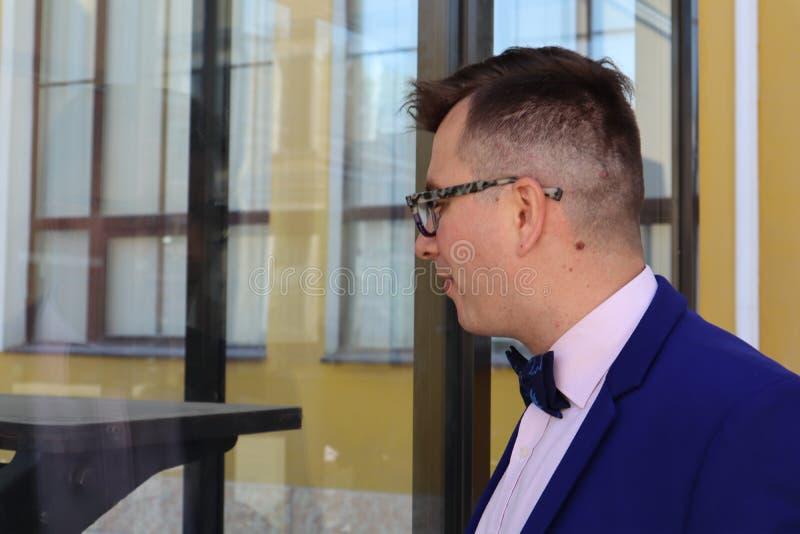 Mężczyzna w kostiumu błękitnych spojrzeniach przy drukową prasą za szkłem obrazy stock