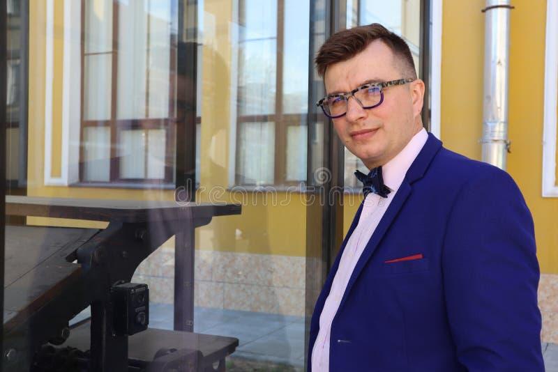 Mężczyzna w kostiumu błękitnych spojrzeniach przy drukową prasą za szkłem zdjęcia stock