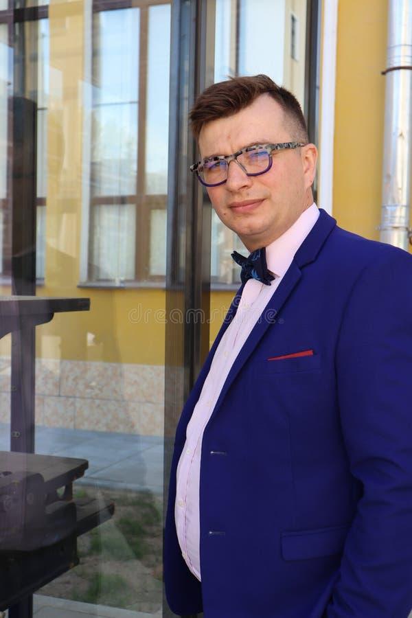 Mężczyzna w kostiumu błękitnych spojrzeniach przy drukową prasą za szkłem zdjęcie royalty free