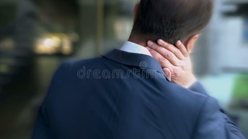 Mężczyzna w kostiumu cierpi od szyja bólu, bezwolnych styl życia przyczyn dordzeniowy problem zdjęcia royalty free