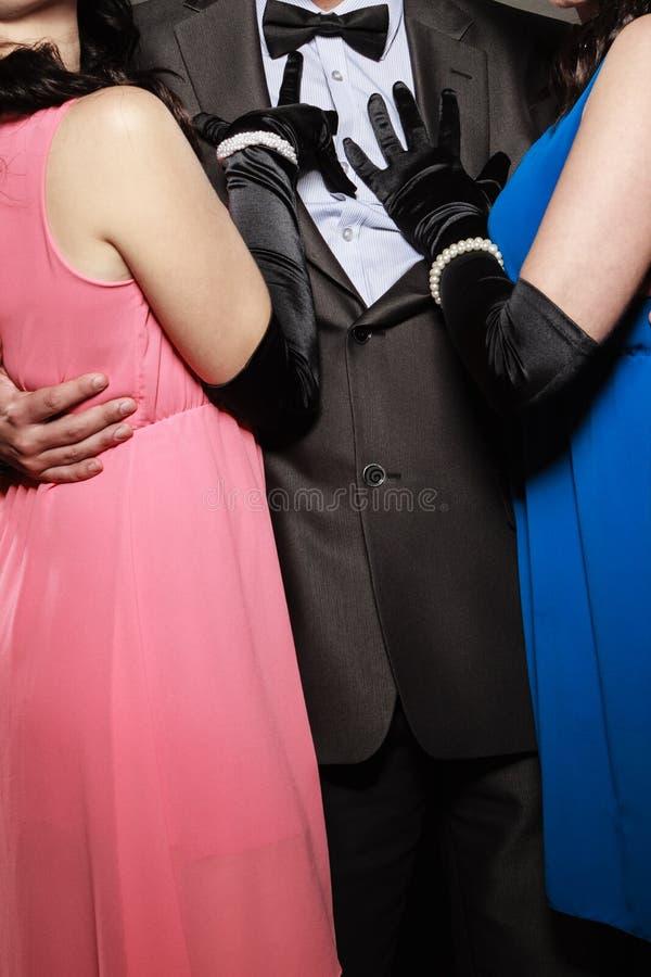 Mężczyzna w kostiumu i dwa eleganckich kobietach w sukniach obraz royalty free