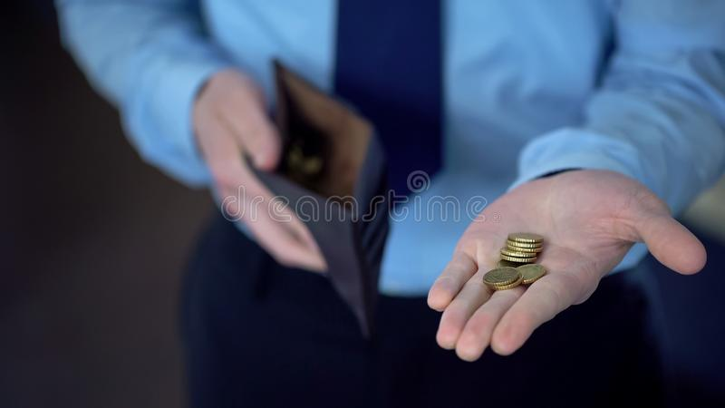 Mężczyzna w kostiumu mienia monetach w otwartej palmie, daje darowiznom, niski dochód, ubóstwo zdjęcia stock