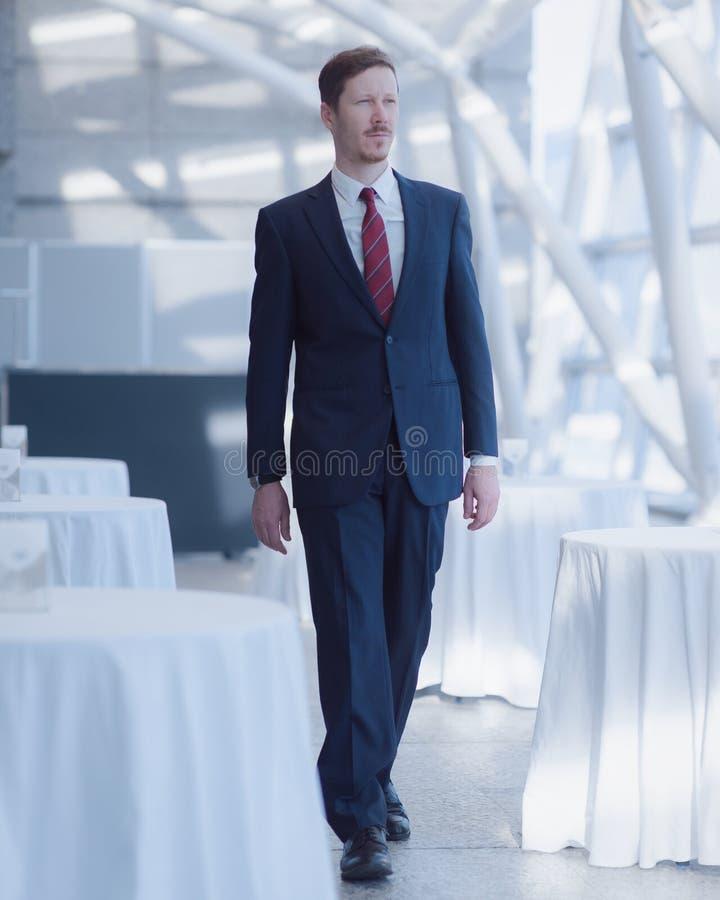 Mężczyzna w kostiumu odprowadzeniu po środku pustych białych stołów obraz royalty free
