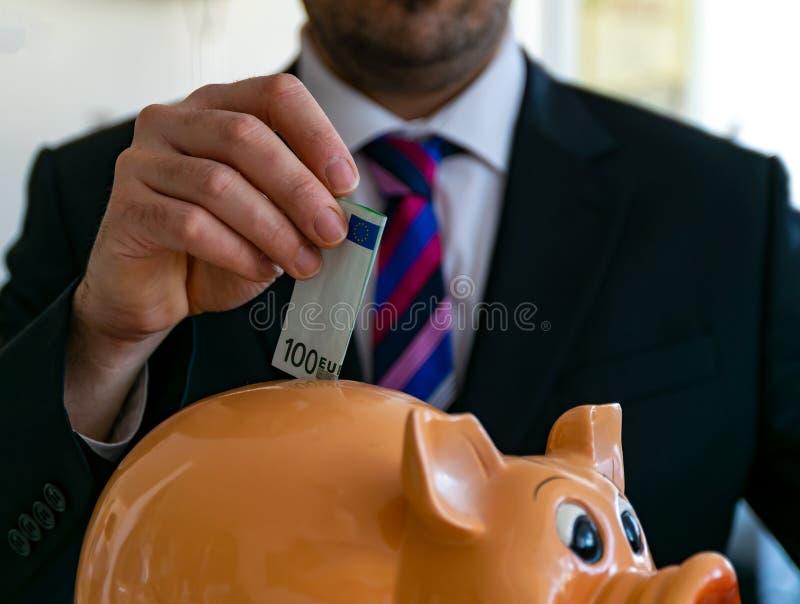 Mężczyzna w kostiumu pcha sto euro rachunków w prosiątko banka obrazy royalty free