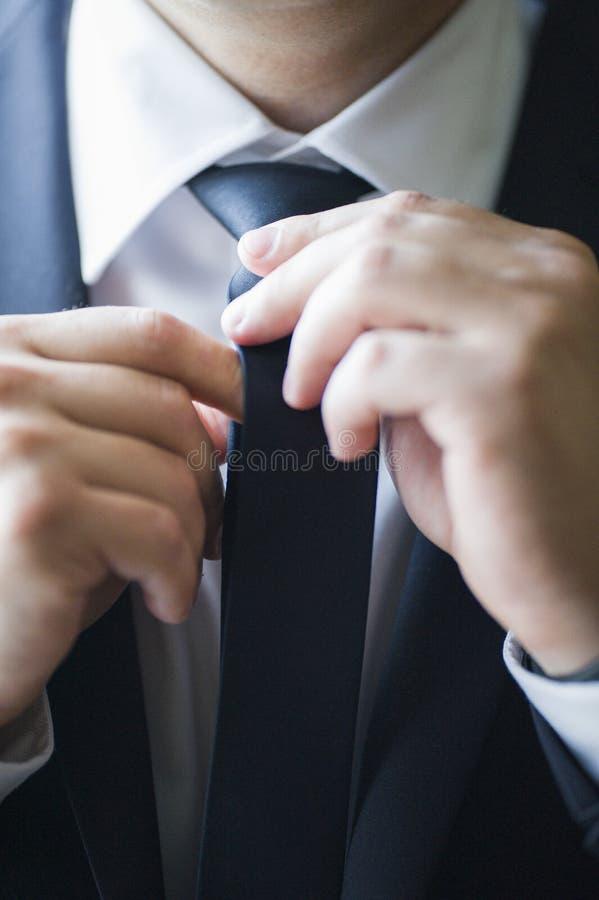 Mężczyzna w kostiumu prostuje jego krawat, zakończenie obraz stock
