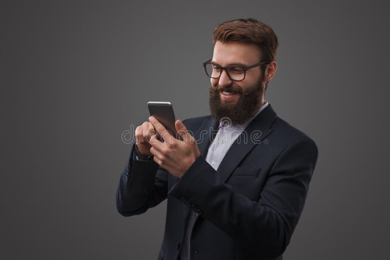 Mężczyzna w kostiumu używać telefon w studiu zdjęcia stock
