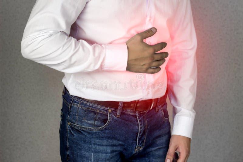 Mężczyzna w koszula białych chwytach dalej podbrzusze, brzuszny ból, zgaga, zakończenie zdjęcia stock