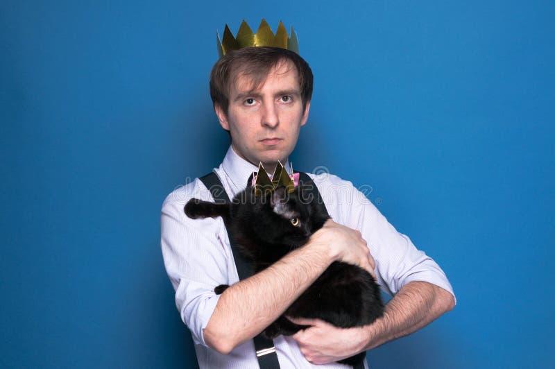 Mężczyzna w koszula, suspender i domowej roboty złotej koronie, trzyma czarnego kota w błyszczącej koronie na błękitnym tle fotografia stock