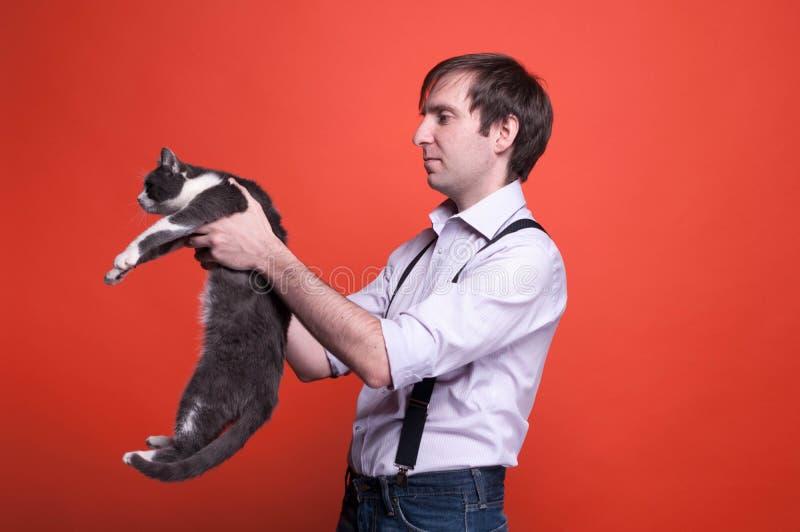 Mężczyzna w koszulowego mienia szarym kocie na szeroko rozpościerać rękach obraz stock